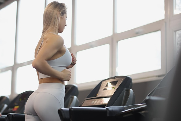 Young woman in sports uniform working out on treadmill in gym regular sports training concept