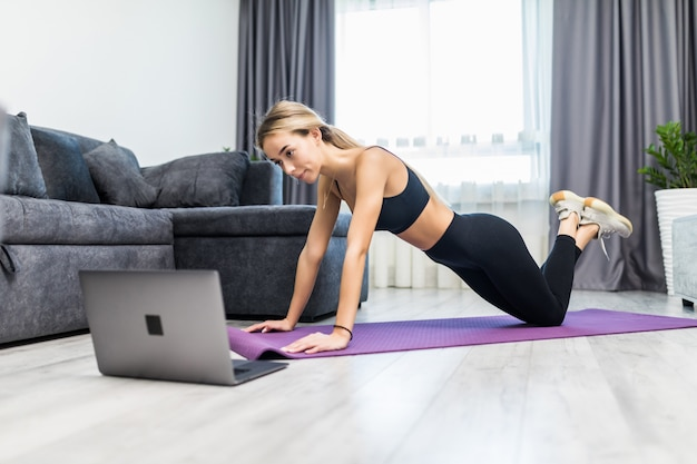 Young woman in sportswear doing push-ups on mat at home. young woman exercising at home in self quarantine due to covid19 pandemic.