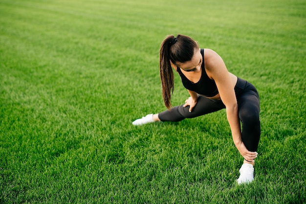 Young woman in sportswear doing warmup before training by stretching her legs in the stadium