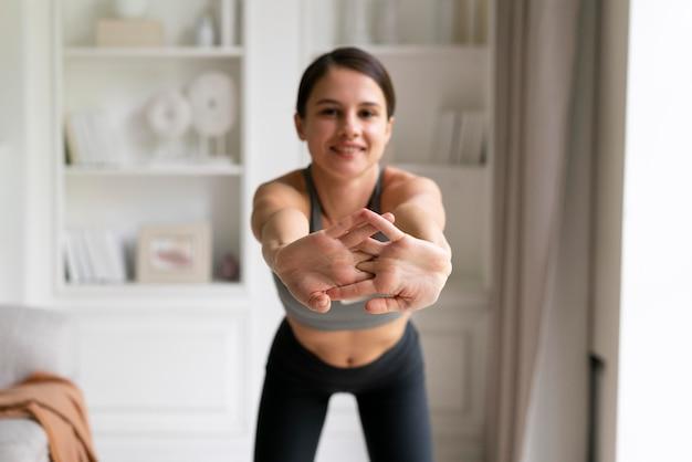 Giovane donna in abbigliamento sportivo che si esercita a casa