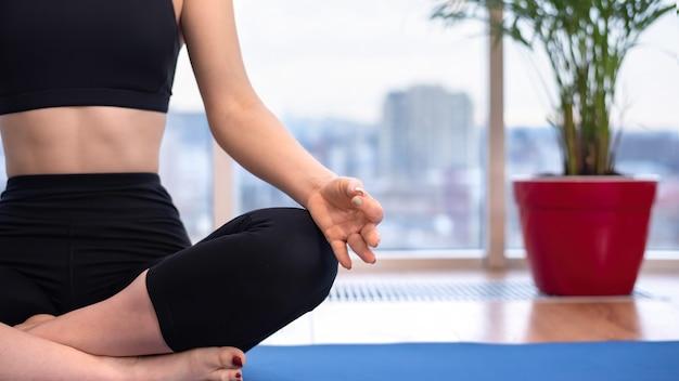 La giovane donna in abbigliamento sportivo sta meditando su una stuoia di yoga