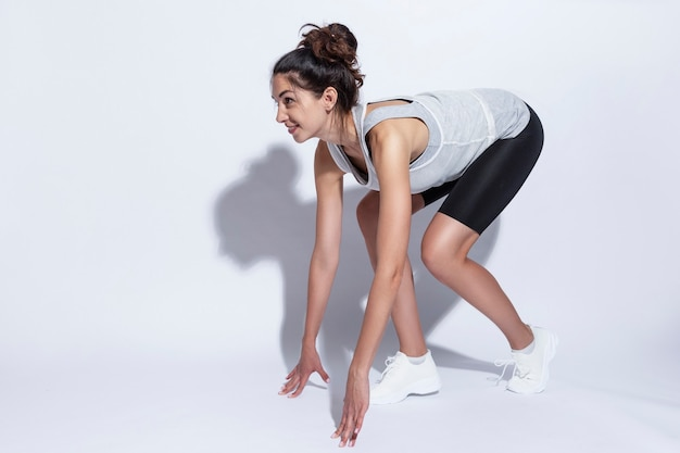 Young woman in sportswear at a low start. beautiful slender brunette. white background. active lifestyle.