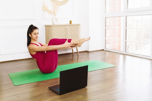 Young woman in sportswear practicing yoga exercising at home with an online trainer doing boat pose paripurna navasana