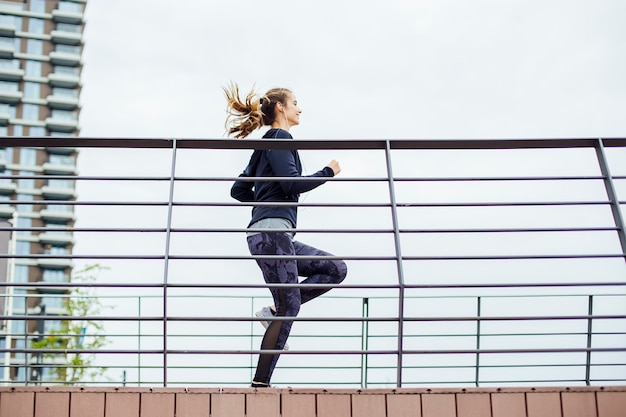 Young woman in sportswear running on the bridge by the river