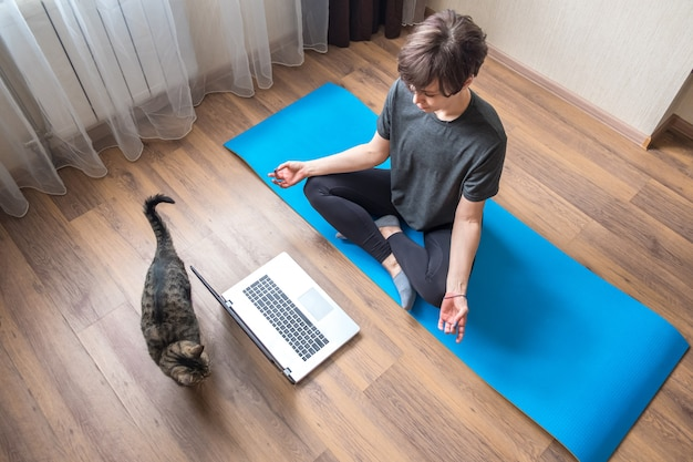 Young woman in sportswear watching yoga online videos on laptop