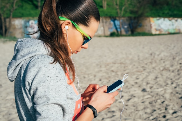 Young woman in sportswear with a hood walking on the beach and listening to music with headphones on a smart phone