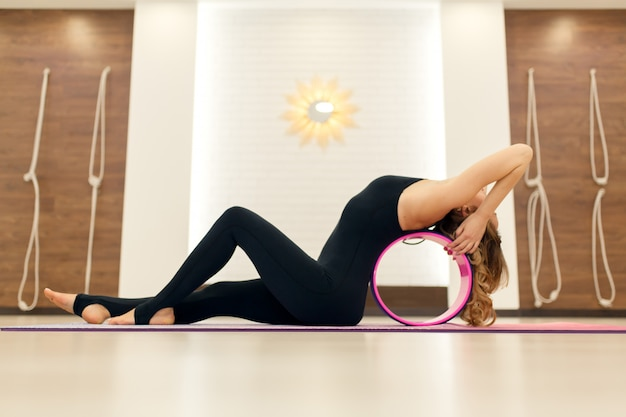 Young woman in a sportswear yoga exercises with a yoga wheel in the gym