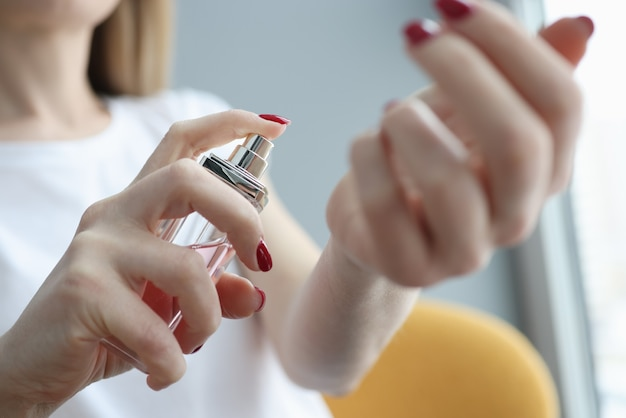Young woman spraying perfume on her hand closeup