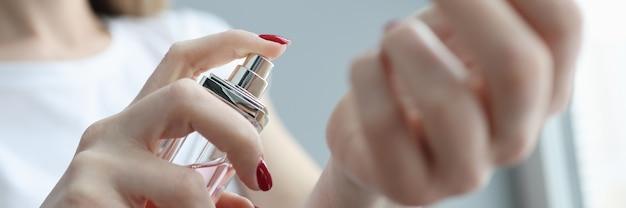 Молодая женщина распыляет духи на ее руке крупным планом