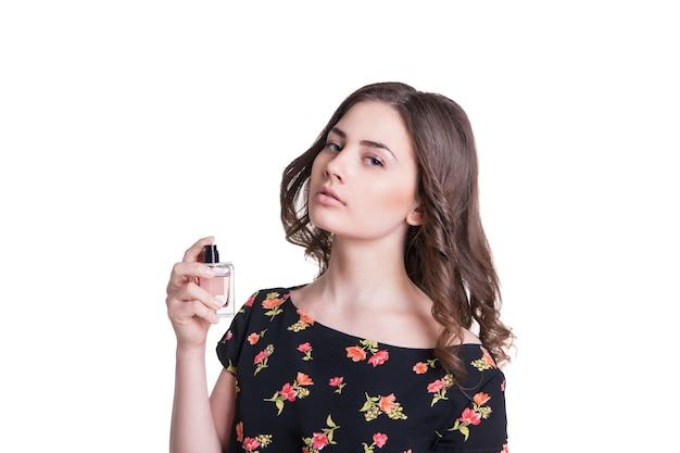 Молодая женщина распыляет духи на шею