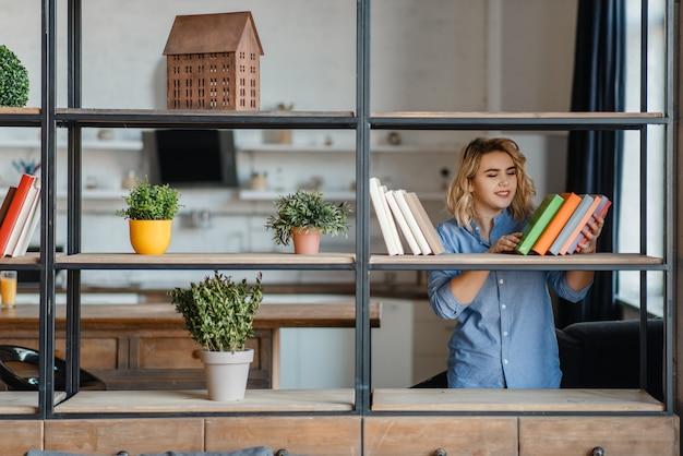 若い女性は棚に家の植物をスプレーします