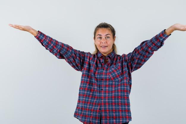 チェックシャツを着て誰かに挨拶し、きれいに見えるように腕を広げている若い女性