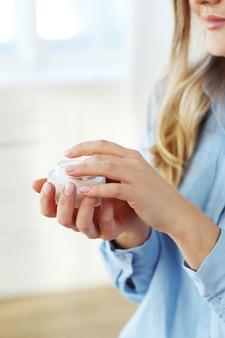 Молодая женщина, распространяя крем для лица. концепция ухода за кожей.