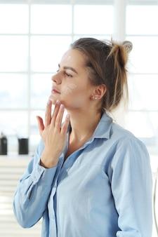 Young woman spreading facial cream. skin care concept.