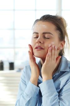Crema facciale di diffusione della giovane donna. concetto di cura della pelle.
