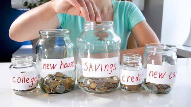 Young woman spreading her money savings in glass jars. concept of financial investment, economy growth and bank savings.