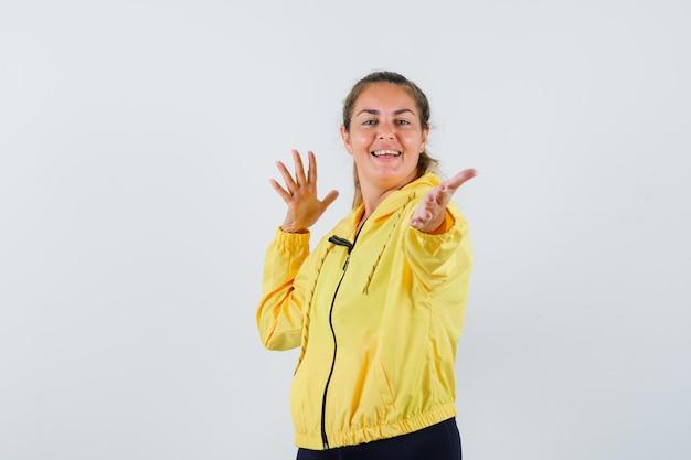 若い女性は彼女の開いた手のひらを黄色のレインコートで前方に広げ、陽気な見ている