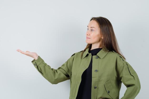 緑のジャケットで何かを見せて、集中して見えるために手のひらを脇に広げている若い女性。正面図。
