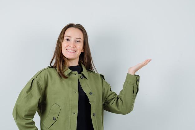 緑のジャケットで手のひらを脇に広げて喜んでいる若い女性。正面図。