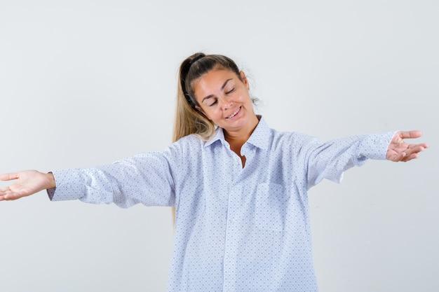 白いシャツを着て誰かを抱きしめ、幸せそうに見えるように手のひらを広げている若い女性