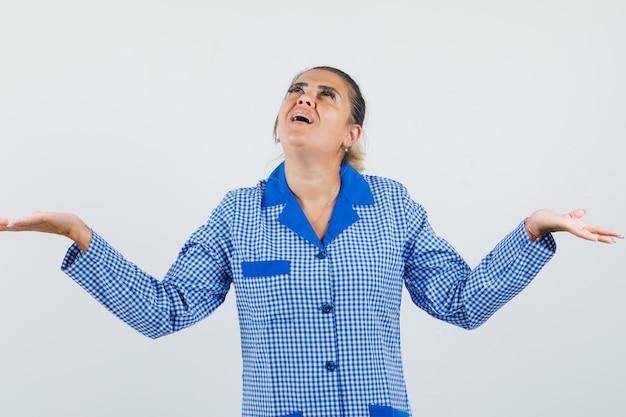파란색 깅엄 파자마 셔츠 위에서보고 놀란 동안 뭔가를받는 것으로 손바닥을 펼치는 젊은 여자. 전면보기.