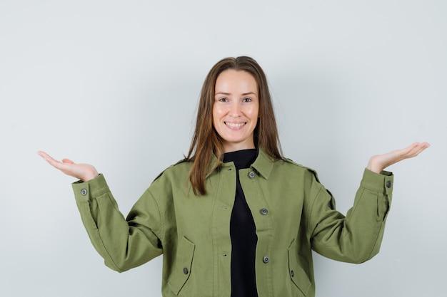緑のジャケットで手のひらを広げて陽気に見える若い女性。正面図。