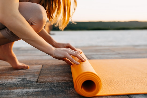 Young woman spreading yoga mat