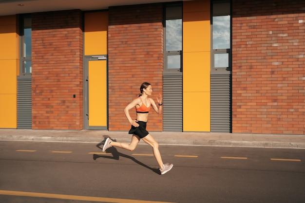 Молодая женщина спринт утром на открытом воздухе. вид сбоку женского бегуна, работающего в городе.