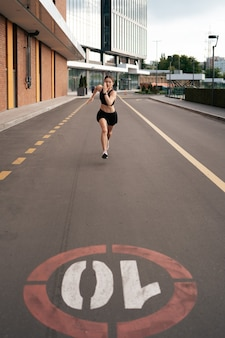 Young woman sprinting in the morning outdoors. top view of female runner working out in the city.