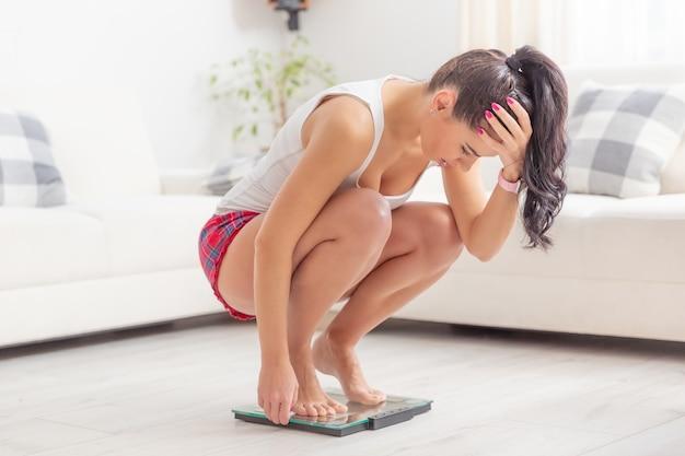 Молодая женщина приседает на весах, держа голову расстроенной из-за набора веса.