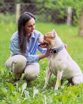 Молодая женщина на корточках и ласкает американского питбультерьера в парке счастливая собака с высунутым языком