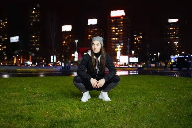 大都市で夜の野外トレーニングの準備をしながらしゃがむ若い女性