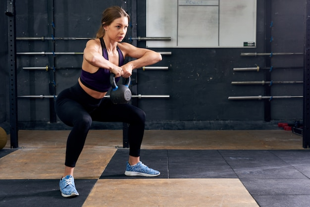 Young woman squatting with kettlebell in gym