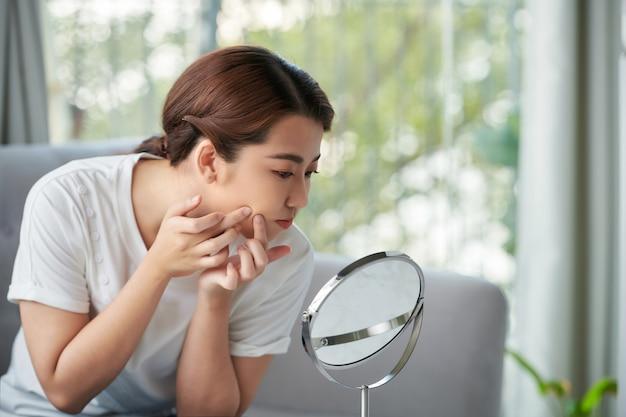 若い女性は鏡の前で彼女のにきびを絞る