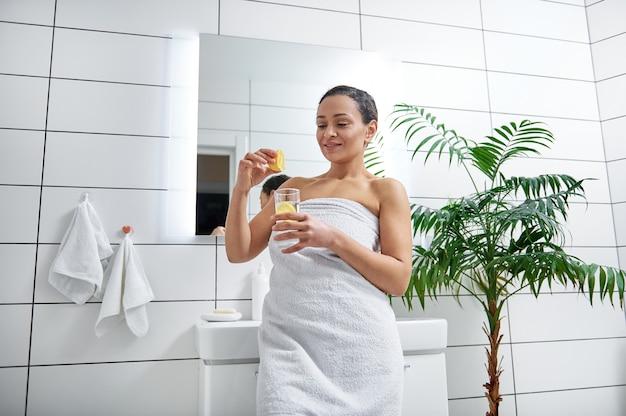 若い女性は彼女の浴室でレモンジュースをコップ一杯の水に絞ります