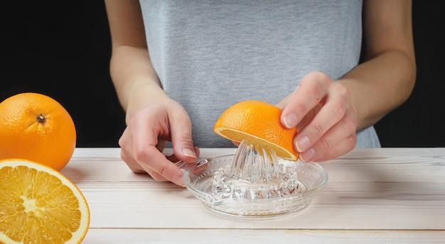 若い女性が手動ガラスジューサーを使用してオレンジジュースを絞る