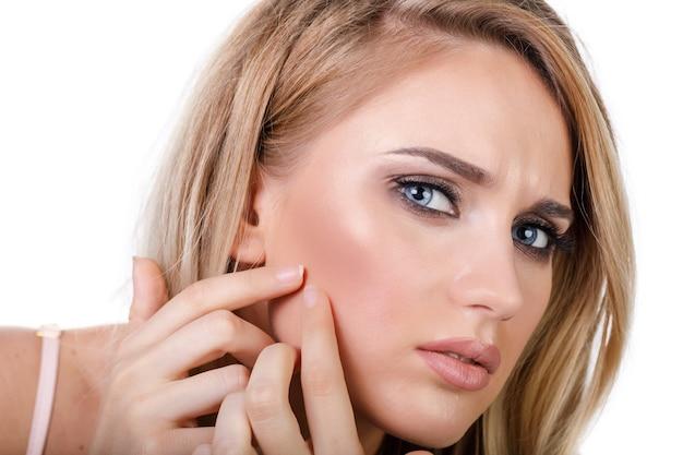젊은 여자는 흰색 배경에 고립 된 거울에 보이는 그녀의 얼굴에 여드름을 좋다고
