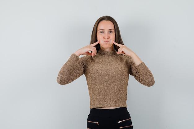 金色のブラウスで頬を絞る若い女性