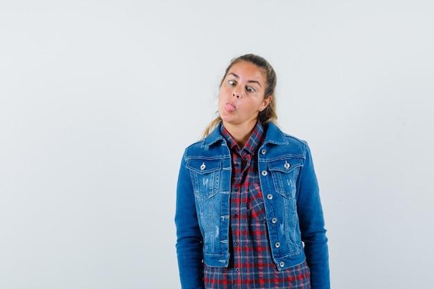 Giovane donna che strabizza gli occhi, sporge la lingua in camicia, giacca e sembra divertente vista frontale.