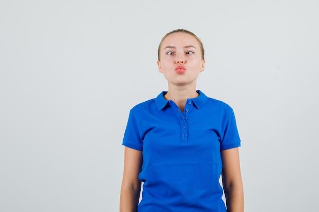 Giovane donna che strabizza gli occhi con le labbra piegate in maglietta blu e sembra divertente