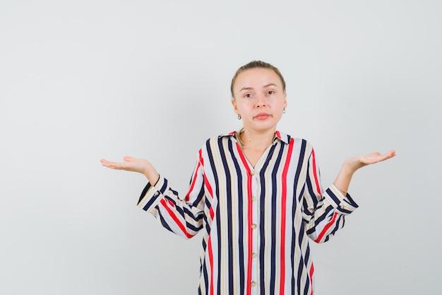 縞模様のブラウスで両手で敗者のサインを見せて、混乱しているように見える若い女性