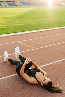 Young woman at the stadium lying down doing sports exercises concept of sports training