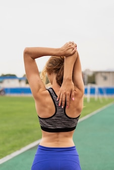 Young woman at stadium stretching