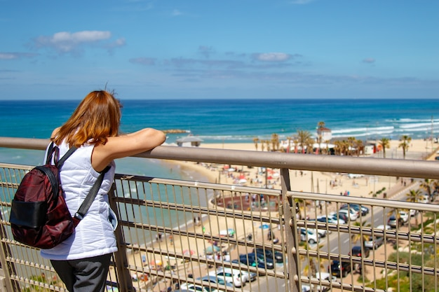 Young woman stand alone at balcony front of sea beach.image for scenery, nature, travel, person.