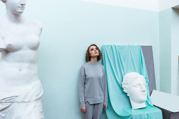 젊은 여자는 벽에 서