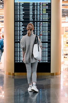 Young woman standing against flight scoreboard in airport.