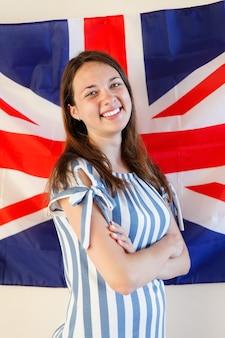 Молодая женщина, стоящая против флага соединенного королевства