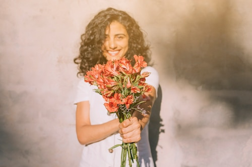 Young woman standing against wall holding alstroemeria red flower bouquet in hands