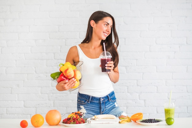 Young woman standing against wall holding bowl of fresh vegetables and fruits and juice