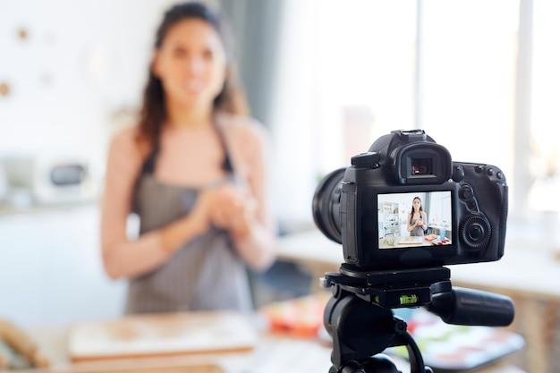 Молодая женщина, стоящая одна на кухне, снимает учебник по выпечке для своего канала блога о еде